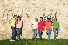 Group of pre teens whispering. Group of pre-teens, kids, playing, flirting and whispering in school playground Royalty Free Stock Images