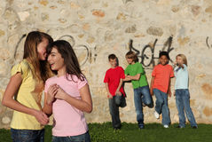Group of pre teens whispering. Group of pre-teens, kids, playing, flirting and whispering in school playground Royalty Free Stock Image