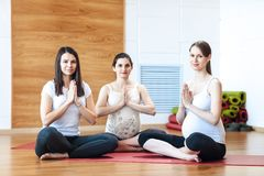 Group of pregnant women doing yoga. Group of pregnant women engaged in yoga in the gym stock images