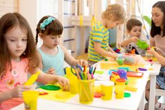 Group of preschool children engaged in handcrafts. Group of preschool kids engaged in handcrafts. Children and teacher in classroom royalty free stock photography