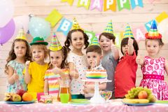 Group of children having fun celebrating birthday party. Kids showing thumbs up sign stock photos