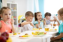 Group of preschool kids have a lunch in daycare. Children eating healthy food in kindergarten royalty free stock photo