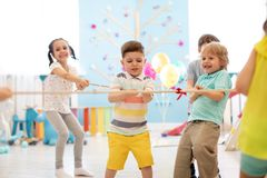 Group of kids play and pull rope together in daycare stock image