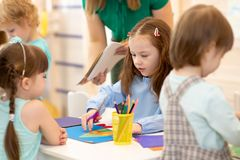 Group of preschool kids working with color paper, sciccors and glue on art class in kindergarten. Group of preschool children working with color paper, sciccors royalty free stock images