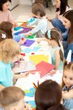 Group of preschool children working with color paper, sciccors and glue on art class in kindergarten stock images