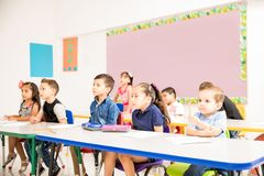 Preschool students paying attention to class. Group of preschool pupils paying attention to their teacher and looking interested in a classroom royalty free stock photos