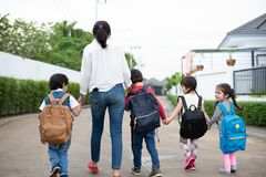 Group of preschool student and teacher holding hands and walking to home. Mom bring her children go to school together. Back to. School and Education concept stock photo