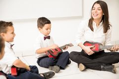 Music lesson in preschool. Group of preschool students and their teacher having a music lesson and playing the guitar in a classroom royalty free stock photography