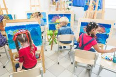A group of preschool students and young teacher in drawing class paint in gouache. mixed race schoolgirl afroamerican stock image