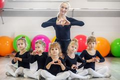 A group of preschoolers and a trainer in dance classes. The concept of sport, education, childhood, hobbies and dance.  royalty free stock images