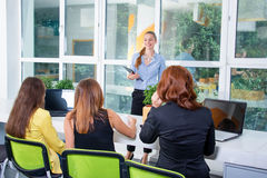 Group of pretty businesswoman working together with new startup project using laptop computer in modern loft, back view royalty free stock photography
