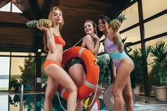 Group of pretty female friends wearing swimsuits having pool party at hotel royalty free stock photo