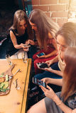Group of pretty young female friends eating together in cafe using smartphones Stock Photography