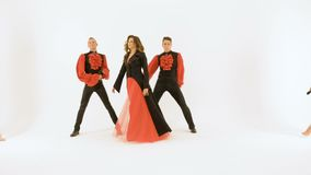 A group of professional actors dancing on a white background. The girl singer in the black dress. Two young men in black. Suits dancing. Two beautiful girls stock footage