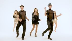Videography of a music video. Actors dance and sing. In studio on a white background. A group of professional actors dancing on a white background. The girl stock video footage