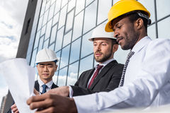 Group of professional architects in helmets working with blueprint outside modern building Royalty Free Stock Photography