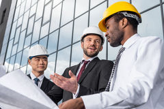 Group of professional architects in helmets working with blueprint outside modern building Royalty Free Stock Photo