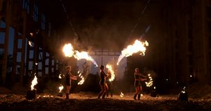 A group of professional artists with fire show the show juggling and dancing with fire in slow motion. stock video footage