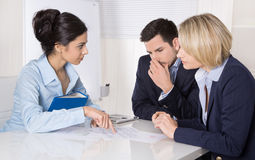 Group of a professional business team sitting at the table talki. Ng together. Male and female people wearing blue clothes Stock Image