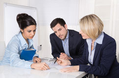 Group of a professional business team sitting at the table talki. Ng together. Male and female people wearing blue clothes Royalty Free Stock Photos