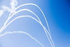 A group of professional pilots of military aircraft of fighters on a sunny clear day shows tricks in the blue sky, leaving beauti stock photos