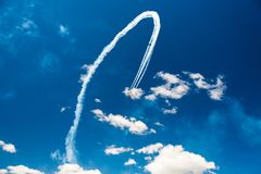 A group of professional pilots of military aircraft of fighters on a sunny clear day shows tricks in the blue sky, leaving beauti. Ful traces of clouds scattered royalty free stock photography