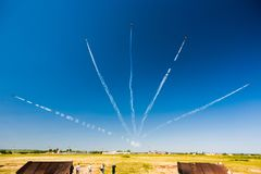 A group of professional pilots of military aircraft of fighters on a sunny clear day shows tricks in the blue sky, leaving beauti royalty free stock image