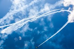 A group of professional pilots of military aircraft of fighters on a sunny clear day shows tricks in the blue sky, leaving beauti royalty free stock photo