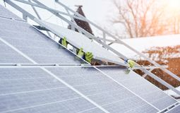 Group of professionals installing photovoltaic solar panels on the roof of modern house during snowy winter time. Alternative energy source renewable Royalty Free Stock Photography