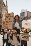 Group of women enjoying the protest. Group of protesters enjoying during a women`s march with signboards. Laughing women holding protest signs for female future royalty free stock photo