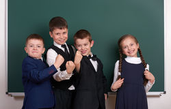 Group pupil as a gang, posing near blank chalkboard background, grimacing and emotions, dressed in classic black suit Stock Image