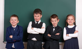 Group pupil as a gang, posing near blank chalkboard background, grimacing and emotions, dressed in classic black suit royalty free stock photos
