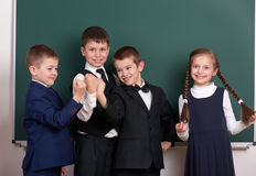 Group pupil as a gang, posing near blank chalkboard background, grimacing and emotions, dressed in classic black suit stock images