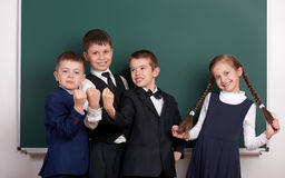 Group pupil as a gang, posing near blank chalkboard background, grimacing and emotions, dressed in classic black suit royalty free stock photography