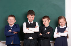 Group pupil as a gang, posing near blank chalkboard background, grimacing and emotions, friendshp and education concept stock photos