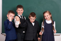 Group pupil as a gang, posing near blank chalkboard background, grimacing and emotions, friendshp and education concept Royalty Free Stock Image