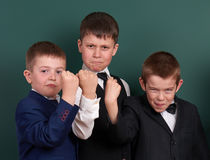 Group pupil as a gang, show knuckle, posing near blank chalkboard background, grimacing and emotions, dressed in classic black sui. T Royalty Free Stock Photos