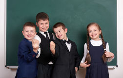 Group pupil as a gang show knuckle, posing near blank chalkboard background, grimacing and emotions, friendshp and education conce. Pt royalty free stock image
