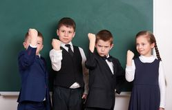 Group pupil as a gang show knuckle, posing near blank chalkboard background, grimacing and emotions, friendshp and education conce. Pt royalty free stock photos
