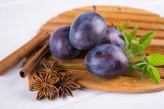 Group of purple plums on a white kitchen board. With fresh mint, cinnamon, anise Royalty Free Stock Photos