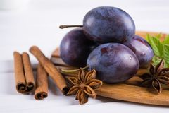 Group of purple plums on a white kitchen board. With fresh mint, cinnamon, anise Stock Photos