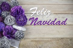 Group of purple and silver Christmas decoration on a wooden background with text in Spanish `Feliz Navidad`. Royalty Free Stock Images
