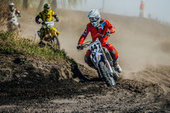 Group racer on a motorcycle turns on a dusty race track Stock Photos