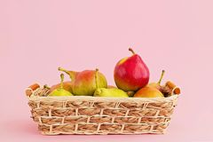 Group of pears in basket on pale pink background. Harvest concept, copy space stock image