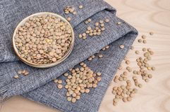 group of raw lentils on a kitchen towel and in a bowl royalty free stock photography