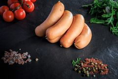 Group of raw short sausages with rucola and tomatoes. Group of raw short thick sausages with pink salt, spices, green rucola and tomatoes cherry on black stock images