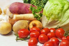 Group of raw vegetable on white,closeup. Group of raw vegetable tomato,potato,lettuce,onion,parsley on white table, closeup Stock Images