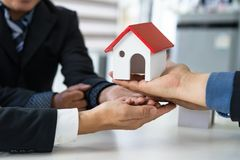 Group of real estate agency hands offer house. stock images
