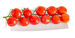 Group of red cherry tomatoes, bunch, vine,  close up, white plat Royalty Free Stock Image