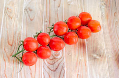 Group of red cherry tomatoes, bunch, vine,  close up, wood backg Stock Photos